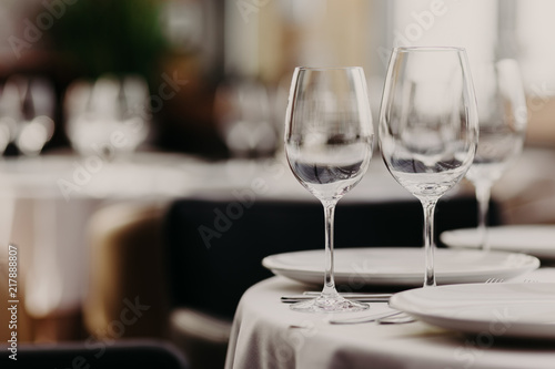 Cozy Restaurant Table Setting With Empty Wine Glasses, White Plates Against  Blurred Background. Banquet