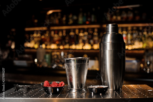 Professional bar equipment, shaker, glass and tongs arranged on the bar counter