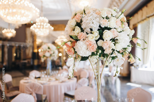 Foto Pink and white wedding bouquet stands in the middle of dinner table
