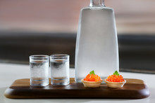 Bottle With Vodka And Two Glass On A Wooden Stand. Near Stand Canapes With Caviar.