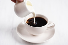 Hand Holding Bottle Of Milk And Pouring In Cup Of Coffee