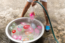Little Boy With Water Hose Filling Colorful Water Balloons In Bucket.