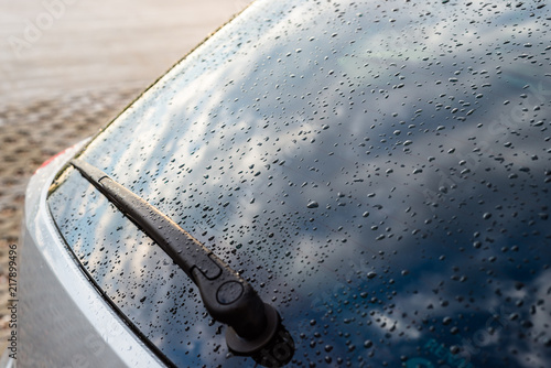 Fotografia Raindrops on a silver car on the rear black window of the car with visible rear wiper