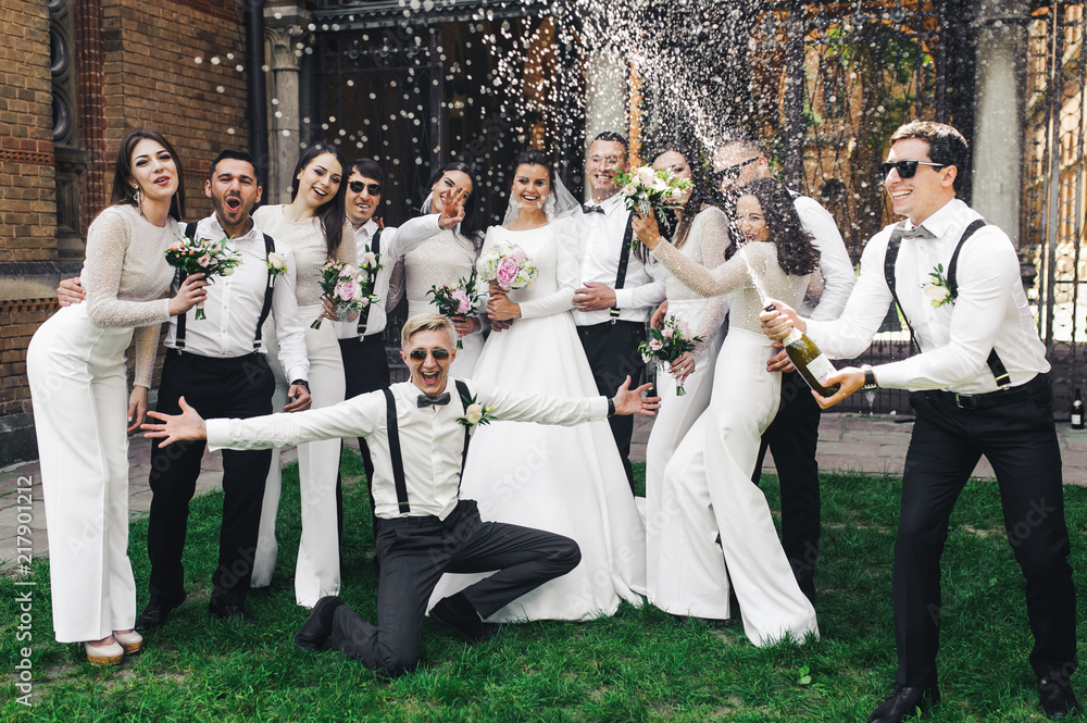 Fototapeta Newlyweds and friends open a bottle of champagne posing on the green lawn