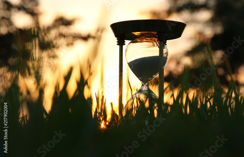Fotografiet  Hourglass in the grass time during sunset. vintage style.