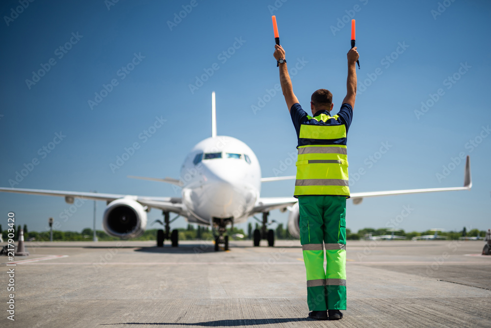 Fototapeta Flight is over. Back view of airport worker meeting passengers and directing the plane. Blue sky, aircraft and runway on background