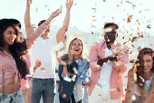 Fotografia Outgoing males and cheerful women throwing confetti having fun outdoor