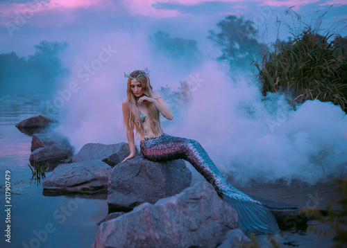 Photo a beautiful mermaid is sitting on the rock in the purple fog