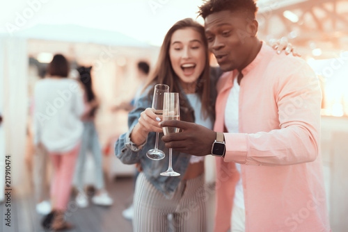 Portrait of smiling male and cheerful woman clanging alcohol beverage while embracing during party