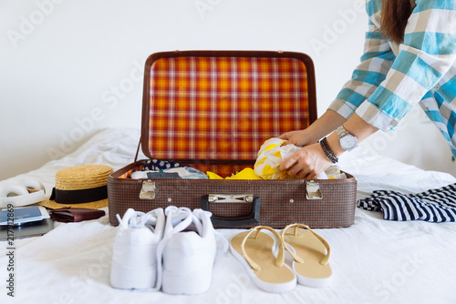 Fotografia  woman hands with watch put clothes in suitcase