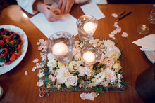 Composition Of White Flowers And Candles On The Table. Wedding Decoration. Woman Signing Papers