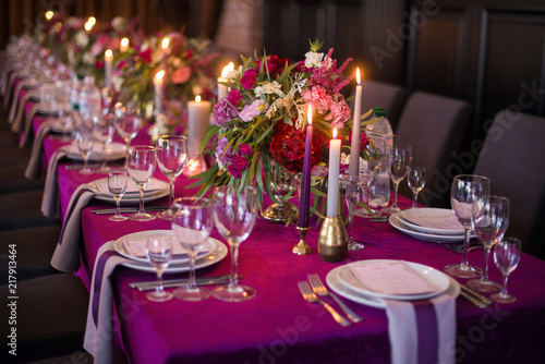 Elegant dark pink wedding banquet table with glasses, dishes and flowers decoration indoors in restaurant Wallpaper Mural