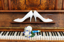 Wedding Art Decoration Concept. Brides High-heel Shoes And Tender Pink Flower Bouquet On The Brown Vintage Piano With Keys.