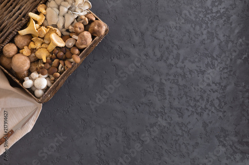 Fototapeta  View from above of wicker basket with forest rare delicious edible mushrooms on a dark textural background, flat lay