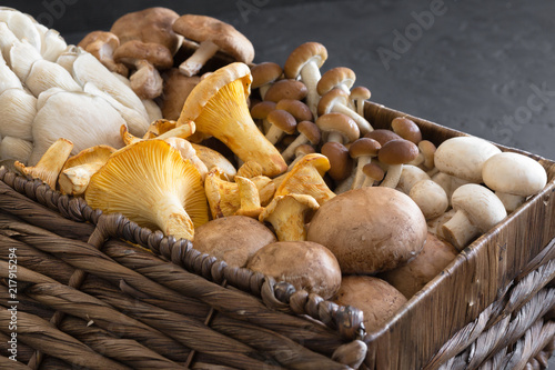 Valokuva Variety of uncooked wild forest mushrooms in a wicker basket on a black background, flat lay