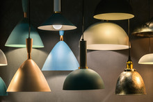 Display Of Many Hanging Lamps With Colorful Lamp Shade Sizes And Colors In Dark Room.