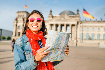 Fototapeta Beautiful young woman looking at map guide while standing in front of Bundestag building at sunset in Berlin. Travel in Germany concept