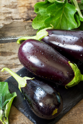 Fresh healthy raw Purple Eggplant on a kitchen wooden table. The concept of Diet menu. Copy space.