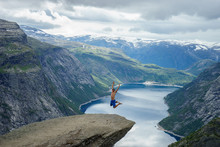 Young Man Jump On The Edge Trolltunga. Norway