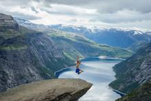 Young Man Jump On The Edge Trolltunga. Norway