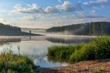 mglisty brzeg jeziora o wschodzie słońca latem z wysoką trawą
