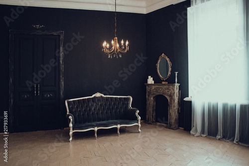 Fotografie, Obraz  Black room in the castle with a window, a chandelier, a sofa and mirror and fireplace