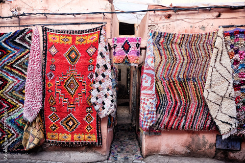 Carpet shop with colourful moroccan rugs on display in a street souk market in the centre of medina in Marrakech, Morocco.