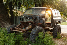 Close-up Of An Old Rusty Jeep Car With A Broken Door And No Wheels On The Background Of A Green Coniferous Forest