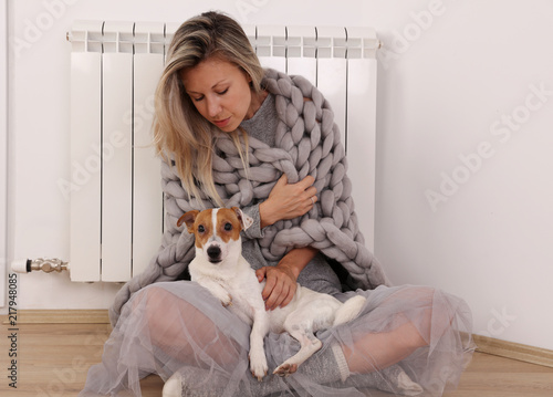 Fotomural Cold home, freezing Woman Wrapped In Blanket Sitting Near Heater with her dog