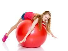 Little Girl Doing Exercises On A Big Ball For Fitness.
