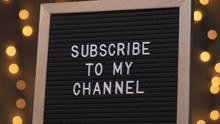 Black Letter Board With SUBSCRIBE TO MY CHANNEL Written On It With White Letters. Camera Rotating Around The Sign Showing The Beautiful Bokeh Balls In The Background.