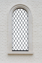 Arched Window With Wrought Iron Lattice And Decorative Figures In The Brick Wall. Window Isolated With Clipping Path