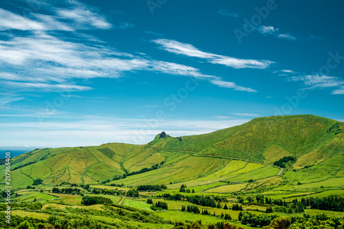Spoed Foto op Canvas Blauw A mountain with green fields and a blue sky with some clouds