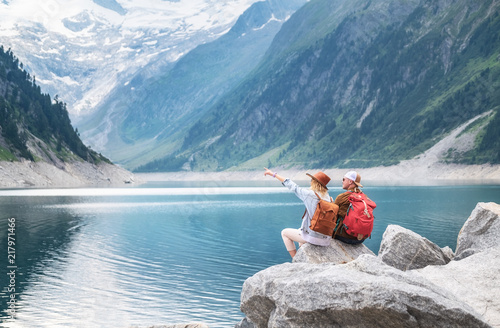 Travelers couple look at the mountain lake. Travel and active life concept with team. Adventure and travel in the mountains region in the Austria