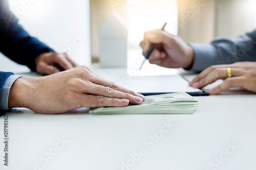 Fototapeta Businessman giving end key to customer after good deal agreement. while loan agreement being approved and calculator, Buy house concept. obraz
