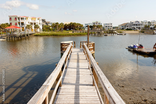 Fototapety, obrazy: Long wooden dock into the inter coastal waterway in North Carolina, with luxury vacation homes and personal water craft