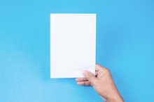 Blank Brochure With Blank In Hand On Blue Background. Mockup For Design