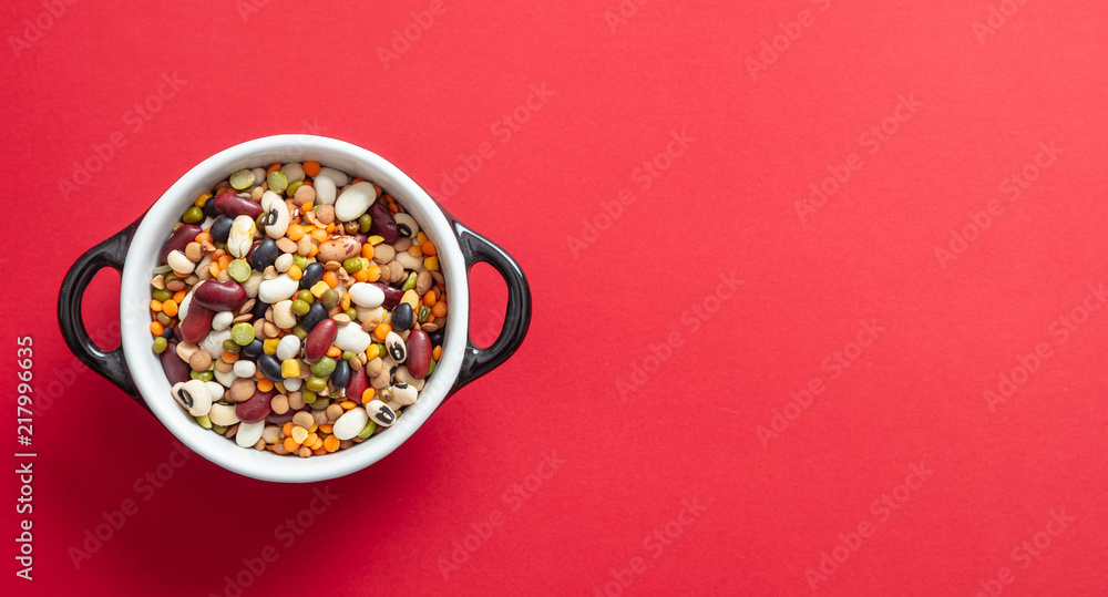 Fototapety, obrazy: Assortment of legumes pulses in enameled bowl on red background, isolated, top view, copy space.