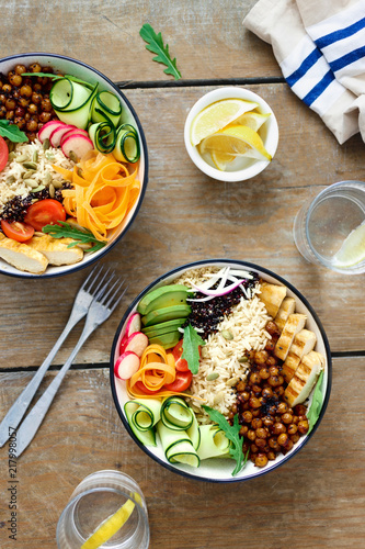 Tuinposter Boeddha Top view two buddha bowl lemon water Clean balanced healthy food concept Chicken grilled steak rice spicy chickpeas black white quinoa avocado carrot zucchini radish tomatoes wooden table