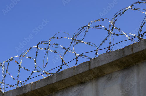 Coils of barbed wire with spikes over the concrete fence closeup