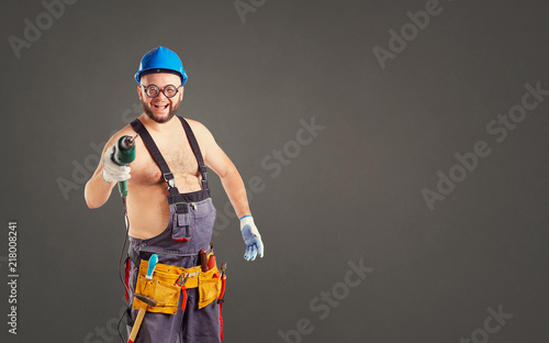 The fat funny man builder with a drill on a background for text.