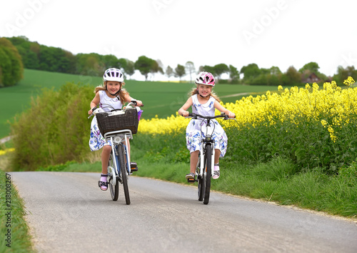 Fototapeta Twin sisters ride their bicycles with scenic landscape around them