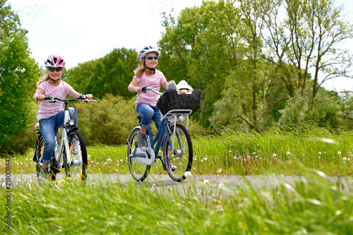 Obraz na plátně  Twin sisters ride their bicycles with scenic landscape around them