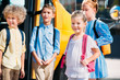 adorable pupils standing near school bus and looking away