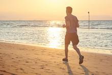 Uomo Che Corre Sulla Spiaggia All'alba