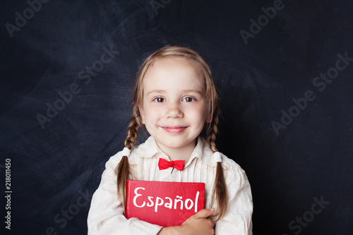 Fotografie, Obraz Beautiful child girl smiling and holding book in spanish language school