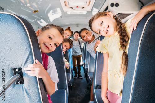 Photo group of cute schoolchildren riding on school bus and looking at camera