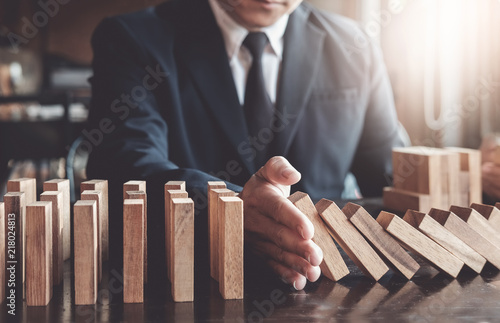 Fotomural  Business risk control concept, Businessman protect wooden block fall to planning and strategy in risk to business Alternative and prevent