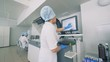 Laboratory facility with a female lab expert working with touchscreen on a Automatic Pharmaceutical Equipment.