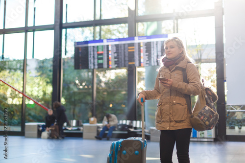 Fotografía  Beautiful young tourist girl with backpack and carry on luggage in international